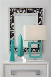 Custom upholstered mirror in silver leaf upholstered in Jill Seale's Black Orchid fabric. Also shown is our Prescott Lamp in turquoise.