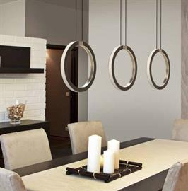 An open ring of light turned on its side offers task and ambient lighting in a single fixture. Sandwiched between round metal frames, the custom acrylic light guide evenly distributes light rays around the ring, sending illumination in all directions.