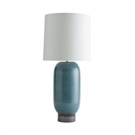 An oblong porcelain body is stacked on a matching porcelain base to create the simple, yet regal Kassy Lamp. The pill-like column features a striking teal reactive glaze finish, further complemented by the base's gunmetal reactive glaze. Topped with an ivory microfiber drum shade. Finish may vary.